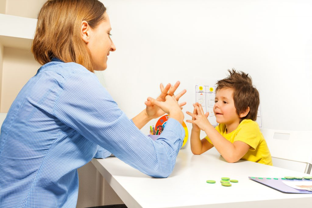 Boy with special educational needs interacts with therapist