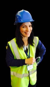 A Female Engineer, smiling wearing and hard hat and hi viz vest