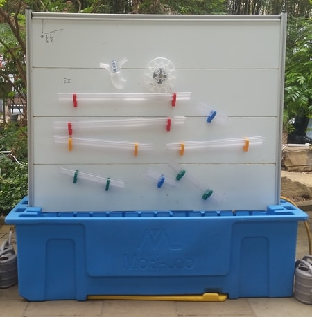 Moti-Lab - a blue reservoir with a magnetically receptive wall attached and magnet gutters wheels and switches