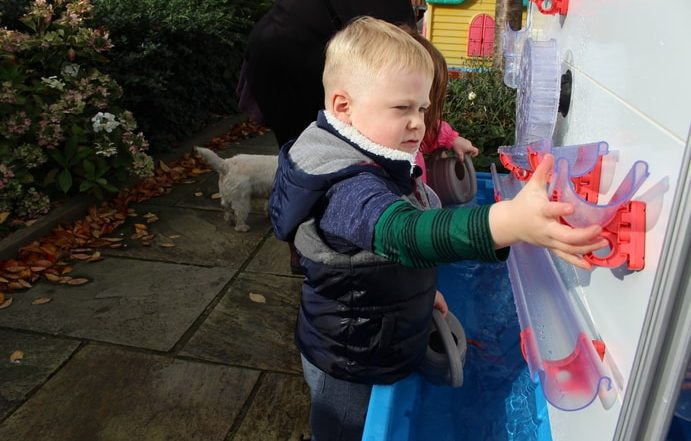 A Young Boy pouring water to learn about EYFS science on Moti-Lab