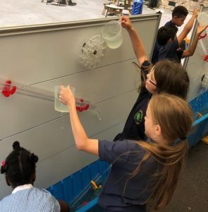 A group of children pouring water to investigate science and maths on moti-lab